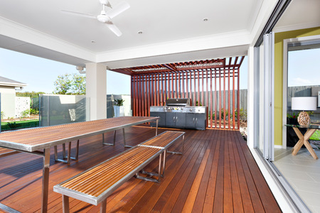 파티오 공간에는 콘크리트 천장이 있으며 지붕은 바깥 쪽을 향하고 있습니다. 아마도 나무 벤치가있는 나무 바닥과 긴 갈색 막대로 만든 테이블이있는