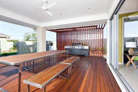 El área del patio tiene un techo de concreto y un techo expuesto al exterior, probablemente área de relajación con piso de madera con bancos de madera y una mesa hecha con largas barras de color marrón, hay conjuntos de pilares de madera fijados en la habitación desde el exterior y al frente
