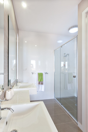 a bathing place: Bathroom has a shower area covering with glass panels attached to the white walls. The area is illuminated by separate lights in the bathing place and others under the silver faucet and white sink near the mirrors. Some towels on the hanger. There is a li Stock Photo