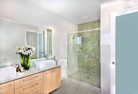 Bathroom of a luxurious house or hotel ready for use with pure white color flowers in the tall and green color vase that made of glass, there are two white washstands with a perfume bottle or hand sanitizer soap with natural herbal cosmetic, underneath a