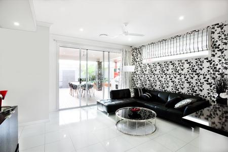 Moderna Sala De Estar Que Incluye Un Sofá Negro Con Almohadas Y ...