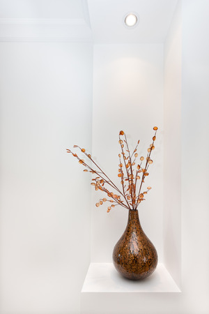 fancywork: Shiny vase is probably made by pasting small wooden parts together shaping as a bottle gourd, there some sticks with buttons fixed to the vase and kept on the wall cupboard