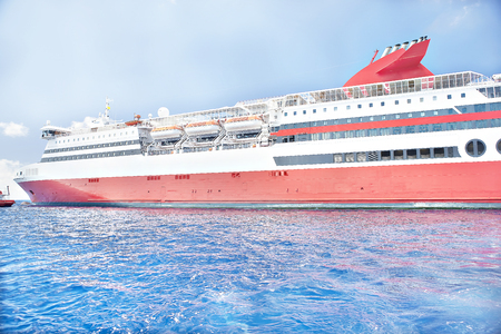 Big ship travelling slowly on water, sunshine arround the area, weather is good, white clouds are beautiful, luxury ships design.