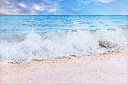 White sea water waves on the sea coast sand close up, with blue water ocean and sky with clouds over the horizon