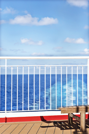 White fence of a ship with blue sky, sea water is colorful, floor is made with woods, sunlight arround the area.