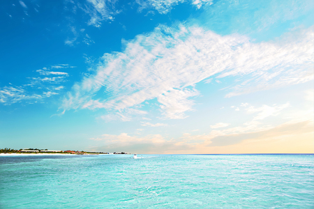 Blue water, sea and blue water, sky with clouds, there is an island from the side with houses and green trees near to the horizon view with yellow color Stock Photo