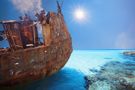 Old and Corroded metal ship at daylight on the blue water sea side with clear sky. Stock Photo