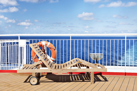 Wooden chair on ship outside floor, sky is colorful and have white clouds, sunlight arround the area. Stock Photo