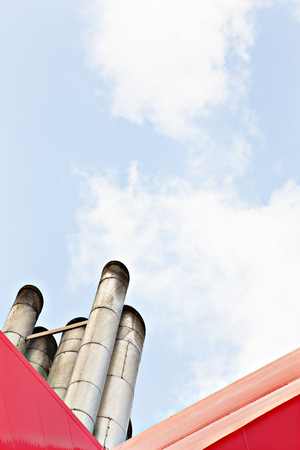 Factory smoke pipes with blue sky, sunlight arround the area, natural view closeup, daytime scene, walls are red color, clouds are white.