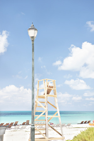 shinning: Natural beach including chairs and lamp stand, weather is clear, daytime scene with sunlight, sea area is shinning, perfect lighting of photo. Stock Photo