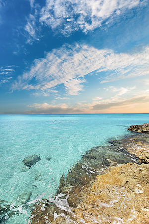 Blue sea and under the white clouds at evening view, the water is clear and covered the yellow and rough ground Stock Photo