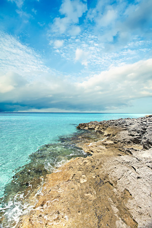 Blue sea and detailed ground coast with cloudy sky in blue color. there are rocks on the sea side with clear water under the busy white clouds Stock Photo