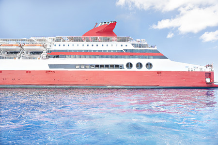 Huge ship with safety boats, sunshine arround the area, weather is good, white clouds are beautiful, luxury ships design.