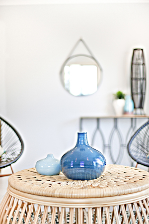 Blue ceramic bottles on brown table, comfortable furnitures with designs, walls are white color, pillows on chairs, inside room of a apartment. Reklamní fotografie