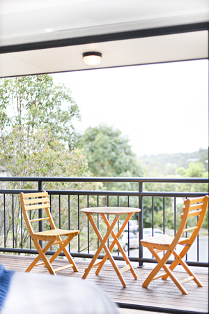 Wooden chairs near tree view, comfortable furnitures with designs, walls are white color, outside area of a apartment.