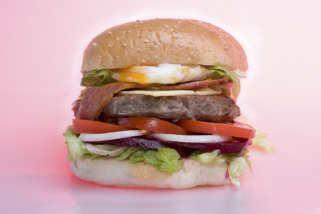 Orange color vegetable and meat mixed bun design, hot burger including fish and vegetables, very tasty look, background is pink color, dining table of a luxury hotel or house . Archivio Fotografico