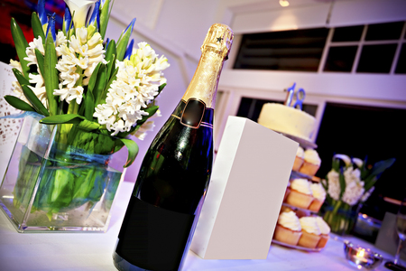 bottle of champaign and chanel perfume placed on table with glass flower pot on side and birthday cake  on the other side Stock Photo