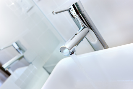 Closeup image of a popular modern bathroom faucet is made by silver, stainless steel and it is dropping water into the white sink and the reflection can be seen through the mirror