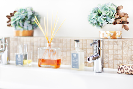 Silver faucet in a washroom with aromatic diffuser perfume and fancy items focusing the stainless steel tap of a modern house or hotel