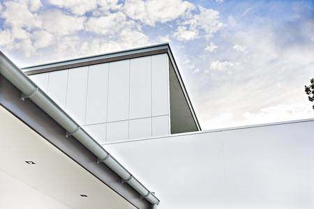 Le bâtiment moderne avec des murs et un toit montre le tuyau d'évacuation sous un ciel bleu avec des nuages blancs Banque d'images