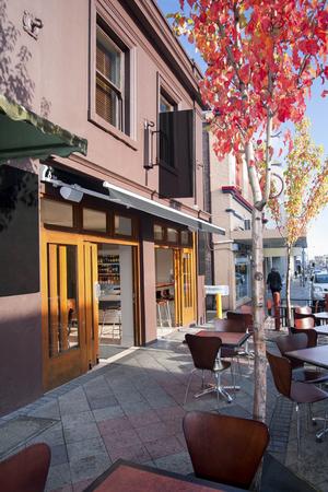 Moderne Restaurants mit Holzstühlen, Himmel ist blau, Sonnenlicht in der Umgebung, natürlich aussehende Pflanzen, Tagesszene, Hotels mitten in der Stadt.