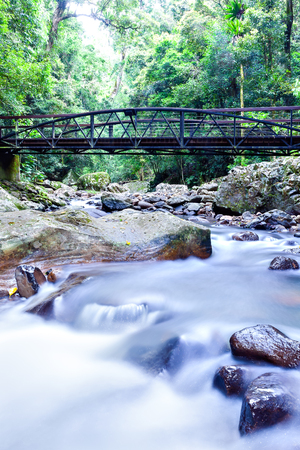 Colorful river running like a smoke through the shiny rocks fast showing the low shutter setup on the camera under the  wooden bridge crossing it through the jungle Stock fotó