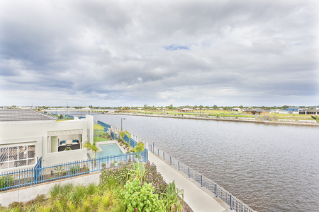 Lake with clear water near apartment and garden,green ground with modern home near riverside, natural looking scene, colorful flowers also plants arround ground, luxury home design, swimming pool near river view.