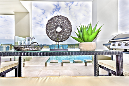 Outdoor kitchen tools near swimming pool, glass cups and flower vase on table, gas cooker near white chair, floor is tiled in brown color.