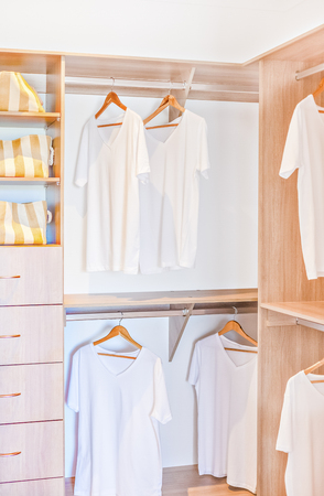 White shirts hanging in the laundry cupboard under shelves. The racks are made in wood and there are drawer and bugs in it. Banco de Imagens