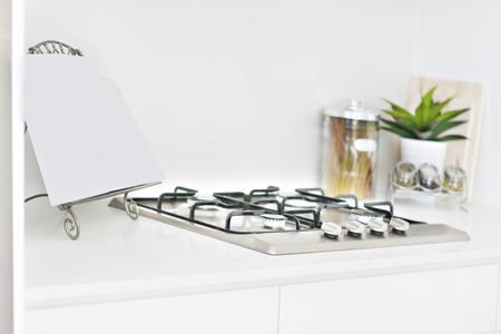 Kitchen tools with white walls and cooker, perfect lightning, evening time at kitchen, gas cooker also some glass bottles on pantry table. Banque d'images