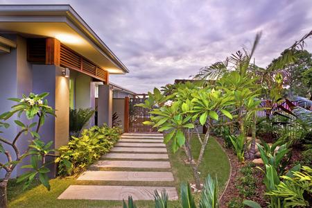 Nowoczesny przydomowy ogród z kolorowym oświetleniem pod fioletowym i zachmurzonym niebem, przy domu zielony trawnik i chodnik obok fantazyjnych roślin, na suficie migają światła