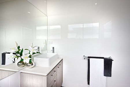 Modern bathroom with a white flowering plant with green leaves beside the hanging towels on the white walls near the mirror