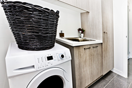 Modern laundry room with a white washing machine and basket made in rattab cables near to silver sink and tap on the wooden counter top