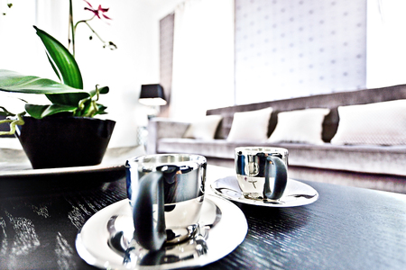 Shiny metal tea cups close up on a black table, there is a black vase with a green leaf plant beside the blurred sofa and pillows in the modern house interior