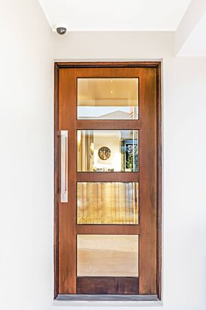 Modern house entrance through the closed wooden door with long handle and made fixed with glass windows, there is a clock on wall, colorful  place also perfect lightning.