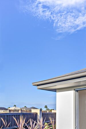 Modern house roof and wall with clear blue sky over the residential area