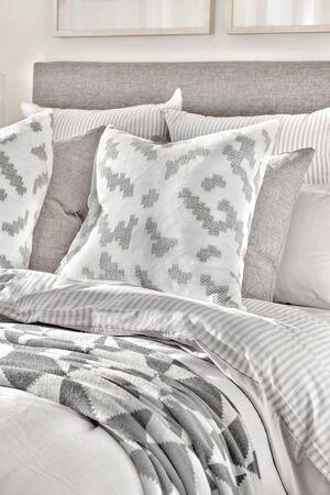 Cama moderna y almohadas con mantas con diseños abstractos de cerca en una casa de lujo Foto de archivo