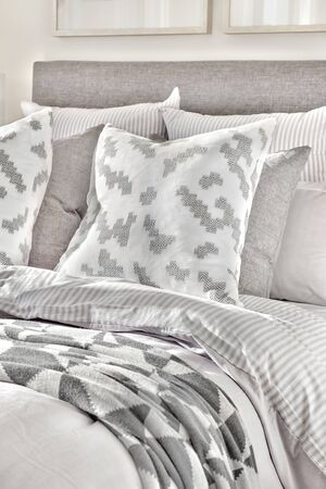Modern bed and pillows with blankets with abstract designs close up in a luxury house