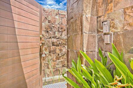 Stone wall entrance with an old wooden door in luxury house Stockfoto