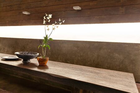 Flowering plant in a vase and other fancy items on the wooden table and illuminated from sunlight through the window