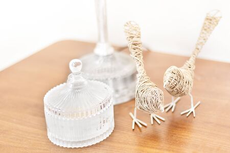 White perfume bottle made in glass beside a  thread yarn birds on the wooden table surface with a brown color as a close up in front of the white walls
