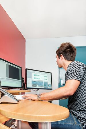 Boy or a college student works with the computer for doing the editing