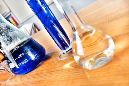 Science equipment in a laboratory, including beakers and tubes with blue liquid on a wooden table closeup