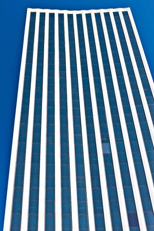Dark blue windows with white lines  of a modern building with the dark sky low angle shot