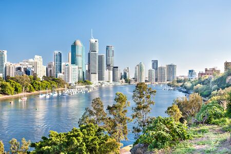 Blue water river surrounded by trees beside a modern cityscape including lots of tall buildings  under blue sky called Brisbane City, Queensland, Australia.