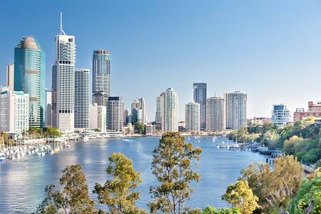 Huge Brisbane City with tall buildings among green trees beside a blue water river and under blue sky in Queensland, Australia.