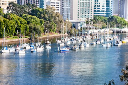 Boats on the blue water river running beside green tress and Brisbane City, Queensland, Australia. Stockfoto