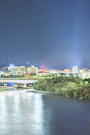 Night city with a forest and lights spread over the sky, giving bright lights behind a river and colorful flares in Brisbane, Queensland, Australia.