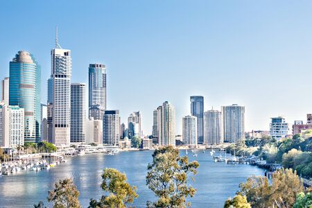 Modern city with blue sky and Brisbane river surrounded by trees