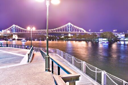 Lakeside and stone road beside a river at night with long bridge that illuminated with purple lights from Brisbane City, Queensland, Australia. Imagens - 131853210